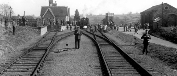 Shows a black and white photo of Thornbury Railway Station with people on the track posing for a photo